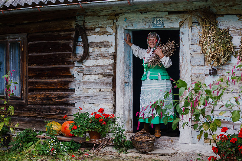 Starsza kobieta stojąca przed chatą Rzeszów